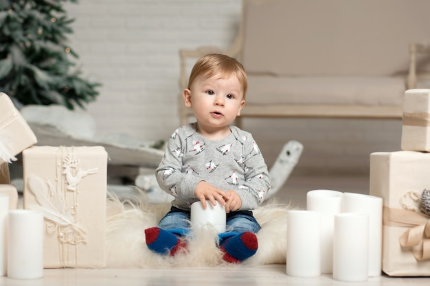 Portrait of a cute toddler playing on the floor near a christmas tree