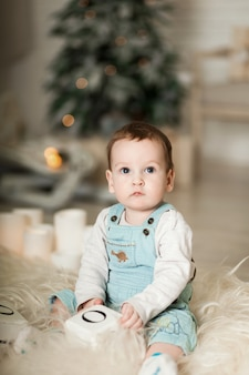 Portrait of a cute toddler playing on the floor near a christmas tree.