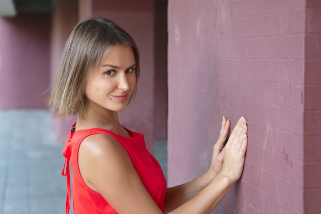 Portrait of cute tricky young woman leaning with her hands against the wall
