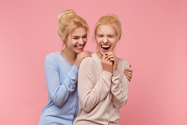 Portrait of cute twins blondes who are never bored together, because they always joke and have fun. stads over pink background.