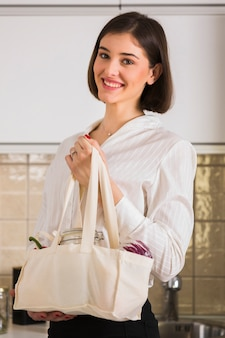 Portrait of cute woman holding groceries bag
