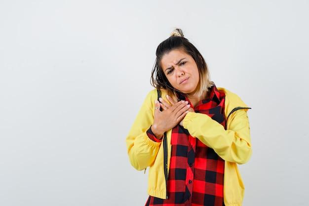 Ritratto di donna carina che si tiene per mano sul petto in camicia, giacca e guarda cupa vista frontale