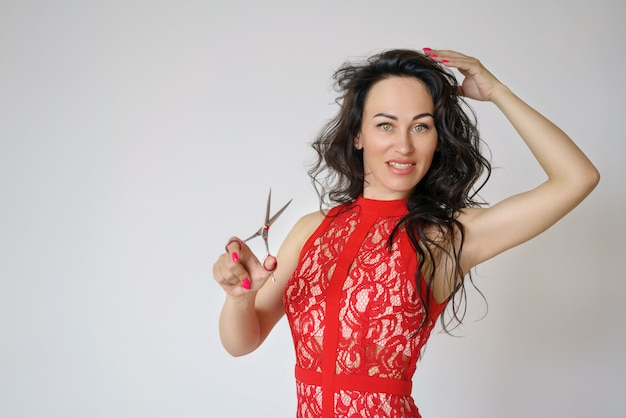 Portrait of a cute woman in a red dress with long hair holding a pair of scissors in her hand on a light