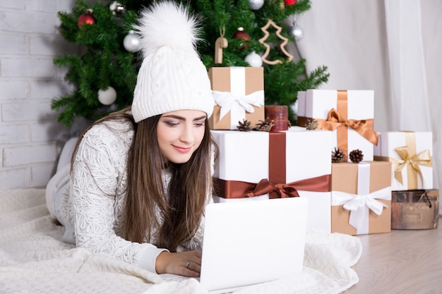 Portrait of cute woman using computer near decorated christmas tree