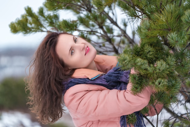 Portrait of cute woman with flowing long curly brunette hair and red lips, dressed in beige jacket with blue scarf. caucasian young woman poses near evergreen coniferous tree in winter season.