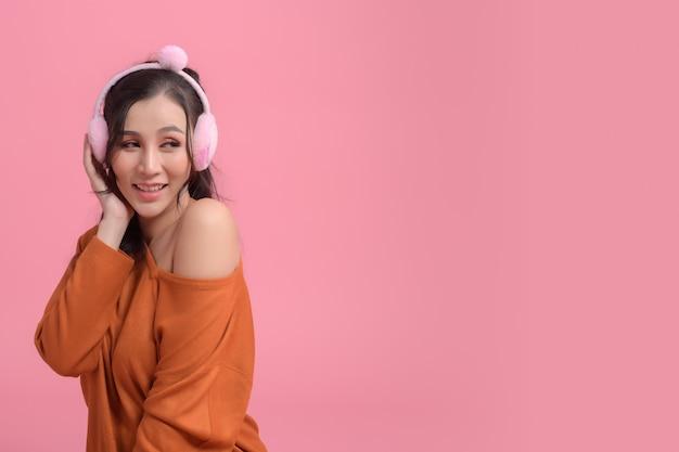 Portrait of cute women with  headphones wearing orange sweater on pink