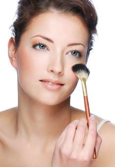 Portrait of cute young adult woman cleaning face after applying make-up