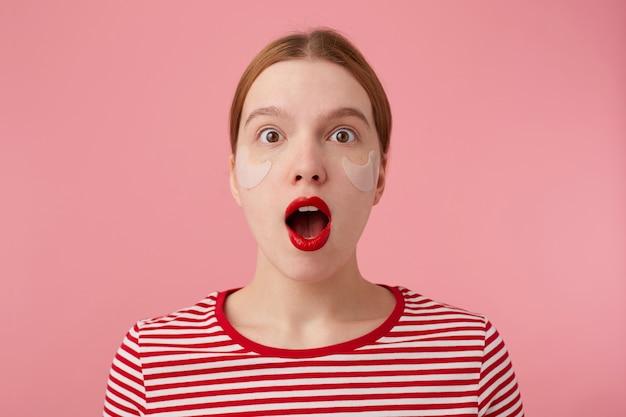 Ritratto di carina giovane signora dai capelli rossi stupita in una maglietta a righe rosse, con labbra rosse e con macchie sotto gli occhi, guarda con la bocca spalancata e gli occhi si leva in piedi.