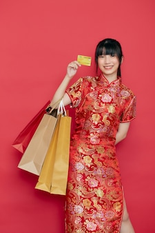 세로 귀여운 젊은 아시아 여자는 빨간 벽에 중국 새 해 쇼핑 가방과 신용 카드와 중국 드레스를 착용