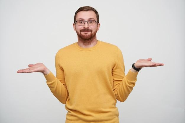 Ritratto di giovane uomo barbuto carino in occhiali con capelli corti castani che scrolla le spalle con le braccia aperte e tiene le labbra piegate mentre si trova