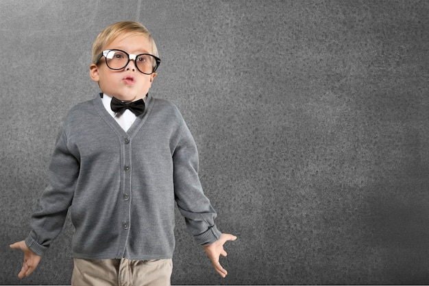 Portrait of a cute young boy in  glasses thinking over background