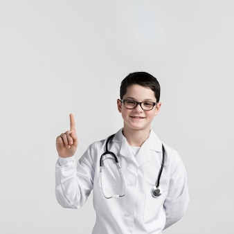 Portrait of cute young boy pointing up