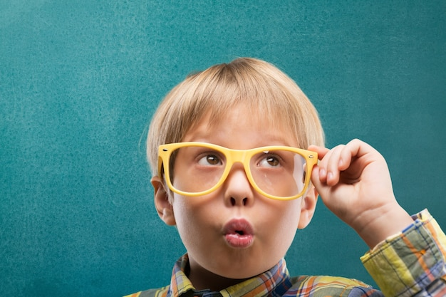 Portrait of a cute young boy with glasses isolated on  background. studio shot.