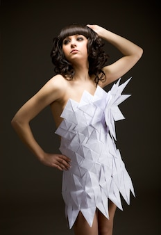 Portrait of a cute young brunette girl in an origami dress