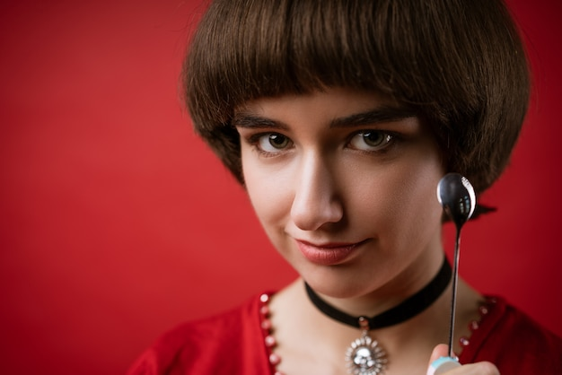 Portrait of a cute young european woman close-up holding a empty spoon in her hand near her face, on a red background