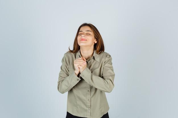 Ritratto di una giovane donna carina che si stringe le mani sul petto in un gesto di preghiera in camicia e guarda grato vista frontale