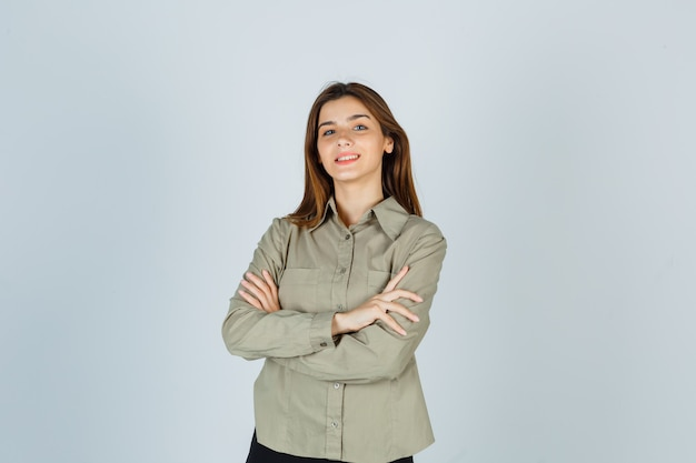 Ritratto di giovane donna carina che tiene le braccia conserte in camicia e guarda allegra vista frontale