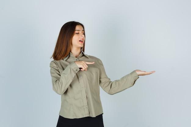 Ritratto di una giovane donna carina che punta il palmo aperto in camicia, gonna e sembra allegra vista frontale