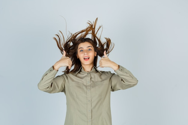 Portrait of cute young female showing double thumbs up while posing with flying hair in shirt and looking blissful front view