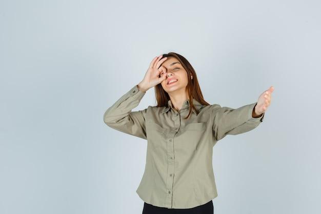 Ritratto di una giovane donna carina che mostra un segno ok sull'occhio, invita a entrare in camicia e sembra felice vista frontale