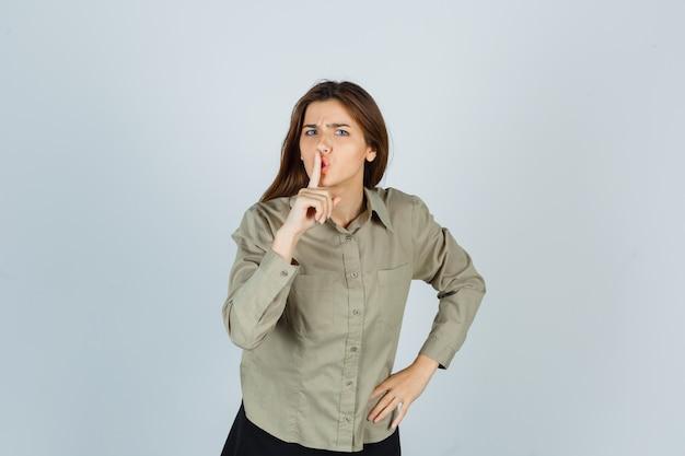 Ritratto di giovane donna carina che mostra gesto di silenzio in camicia e sembra una seria vista frontale