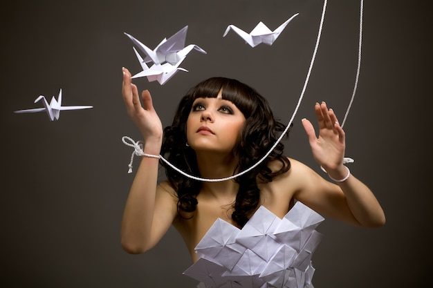 Portrait of a cute young sad girl in origami dress with moving arms like a puppet