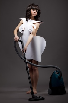 Portrait of a cute young slim girl in origami dresses vacuuming with a vacuum cleaner on a gray background