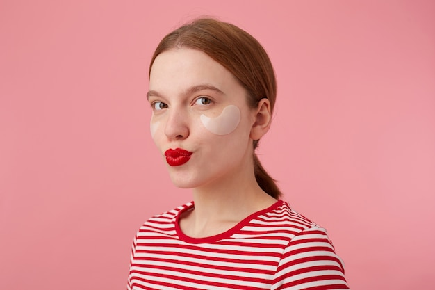 Ritratto di carina giovane ragazza dai capelli rossi sorridente con labbra rosse e con macchie sotto gli occhi, indossa una maglietta a righe rosse, guarda e manda un bacio, si alza.