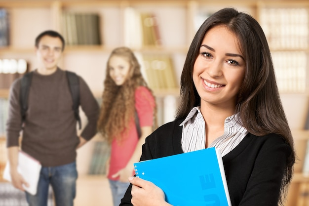 Portrait of a cute young student girl holding book, isolated on background