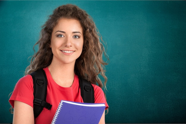 Portrait of a cute young student girl holding colorful notebook, isolated on background