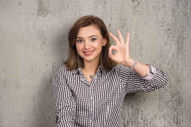 Portrait of a cute young woman showing ok sign with fingers and looking to front