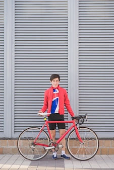Portrait of a cyclist athlete standing against a gray wall with a red road bike