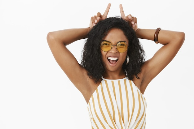 Portrait of daring energized and confident funny young african american woman in sunglasses and striped top showing teeth