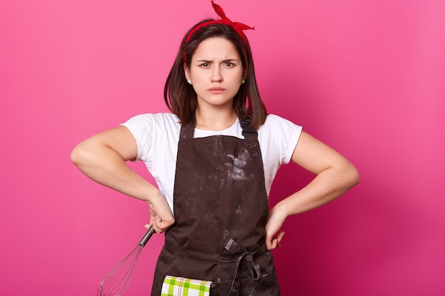 Portrait of dark haired girl in apron soiled with flour, t shirt and red hair band, stands with hands on hips, holds whisk, looks angry, waits husband from supermarket. baker makes delicious cookies.
