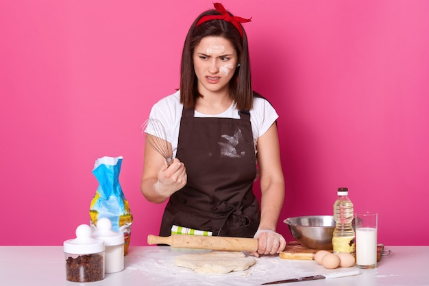 Portrait of dark haired girl in apron soiled with flour, t shirt and red hair band, stands with whisk in hands and feels disgusted from baking pies, wants to have rest. baker makes delicious cookies.