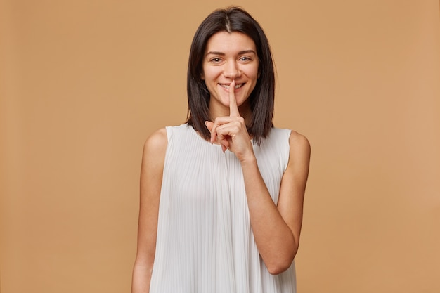 Portrait of a dark haired girl happily smiling showing silence gesture, asks to keep secret putting fore finger on the lips, isolated