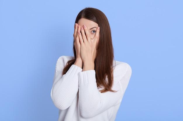 Portrait of dark haired girl hiding eyes under hand while feeling ashamed
