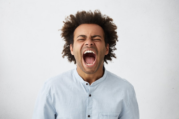 Portrait of dark-skinned african guy with curly hair screaming with wide opened mouth