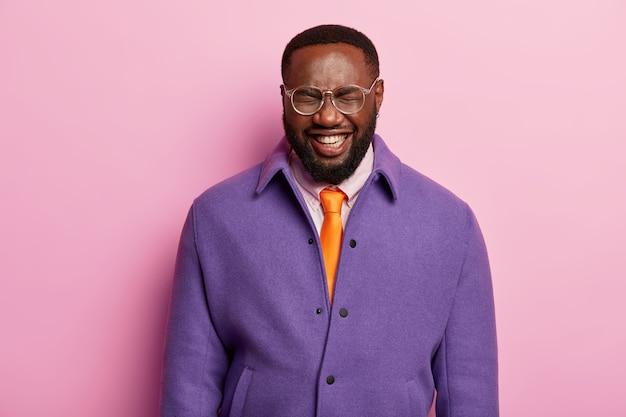 Ritratto di impiegato maschio dalla pelle scura ha una risata isterica, stato d'animo positivo, sorrisi ampiamente, indossa giacca viola, cravatta arancione