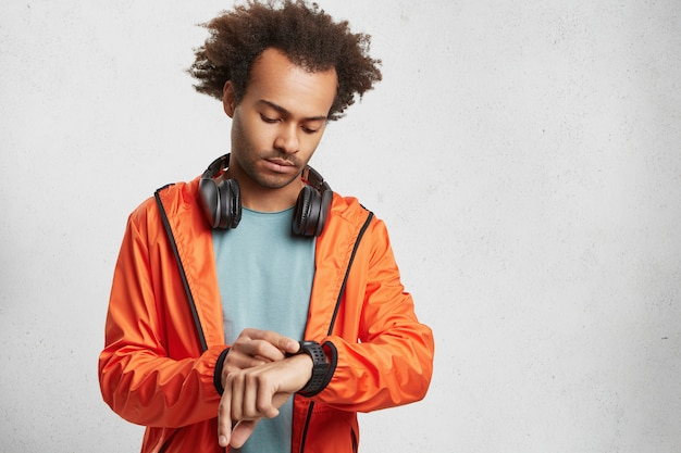 Portrait of dark skinned male student wears orange anorak, looks at watch time