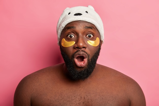 Portrait of dark skinned man stares in stupor wears beauty patches under eyes has thick beard stands shirtless against pink wall looks surprisingly at himself in mirror.