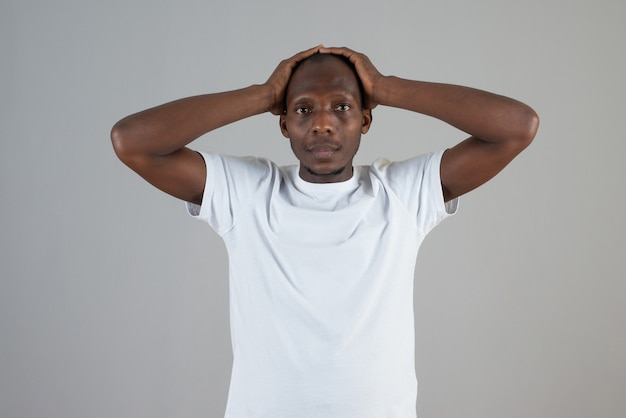 Portrait of dark skinned man in white t-shirt holding his head on gray wall