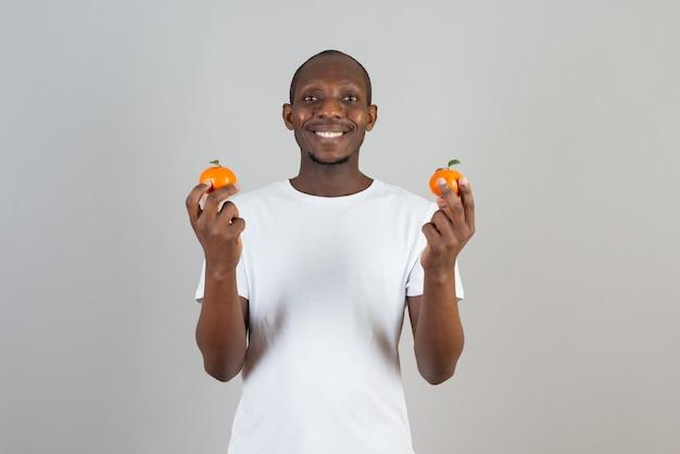 Ritratto di uomo dalla pelle scura in maglietta bianca che tiene i mandarini sul muro grigio