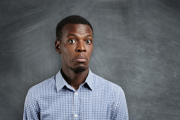 Portrait of dark-skinned student wearing casual shirt looking with surprise, confused and puzzled with teacher's question, standing against blackboard with copy space for your promotional content