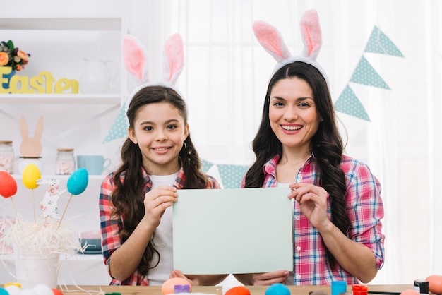 Portrait of daughter and mother showing blank paper on easter day