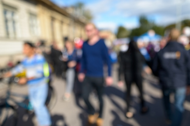 Portrait of defocused crowd of people looking busy in the city street on sunny day