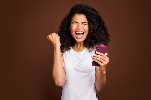 Portrait of delighted afro american girl use smart phone read social media news celebrate victory scram yes raise fists wear white t-shirt.