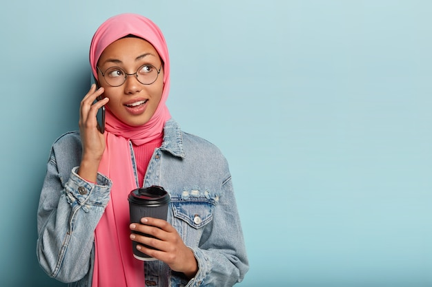 Portrait of delighted arabian woman makes arrangement via cell phone, holds paper cup of coffee, receives good offer, looks aside