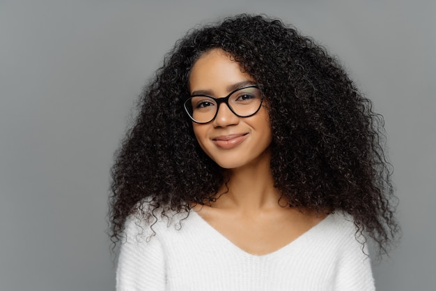 Portrait of delighted beautiful afro woman with bushy curly hair, looks through transparent glasses