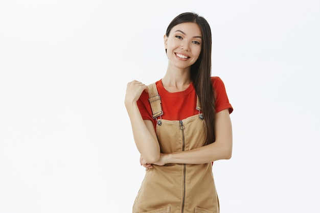 Portrait of delighted charismatic and outgoing asian woman with dark hair in cute brown overalls touching shoulder